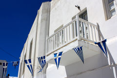 A typical white house with a balcony and Greek triangle flags in. Mykonos, Greece in a sunny day with blue sky on the background Stock Photo