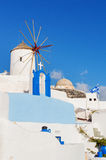 Typical white windmill on street of Oia village Stock Image