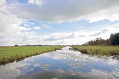 Typical wide dutch landscape in the Netherlands. Typical wide dutch landscape with meadows, water and cloudscapes Stock Photo
