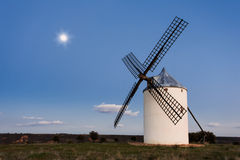 Typical windmill in with the moon at the background Royalty Free Stock Image