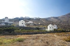 Typical windmill in Santorini. White buildings on a hill, a windmill and trees, is typical for Santorini, Greece. Famous Windmills stock image