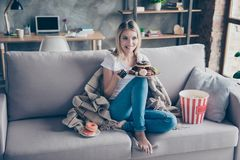 Typical woman weakness! Extremely happy woman is going to watch. Her favourite TV serials, eat donuts and popcorn on holiday Stock Image