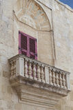 Typical wooden balcony with shutter on old building in Mdina, Ma Stock Image