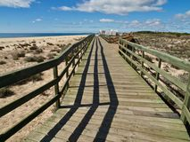 Typical wooden foot path along the beach between Vilamoura and Albufeira stock images