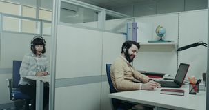 Typical working day in the company of a customer support center , worker happy speaking with them client , and giving hi. To another worker who is walking stock footage