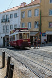 Typical Yellow Vintage Tram in Narrow Street of Lisbon, Portugal.  stock photo