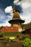 Typically East Frisian windmill in Upgant-Schott. Historical windmill at the street edge in the East Frisian Small Town in Upgant-Schott Royalty Free Stock Photos