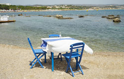 Typically Greek blue restaurant table and chairs beside the sea Stock Image