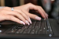 Typing. Young woman´s fingers typing on computer Stock Image