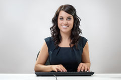 Typing. Woman working at her desk typing Stock Photography