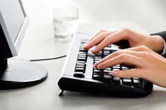 Typing. Photo of female hands on the keyboard of computer typing a letter Royalty Free Stock Photo