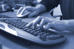 Typing. Male hands typing on keyboard, blue toned stock photo
