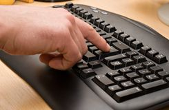 Typing. Pressing Enter Key. Black keyboard on wooden table stock photography