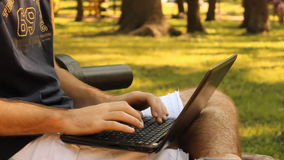 Typing Anonymously. Anonymous man typing on a laptop in the park stock footage