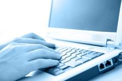 Typing away - green. Woman typing on laptop. High key, selective focus stock photos