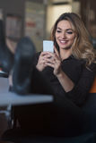 Typing business message. Confident young woman in smart casual wear holding smart phone and looking at it with smile Royalty Free Stock Photo