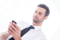 Typing business message. Low angle view of handsome young man in shirt and tie typing message on the mobile phone and smiling Royalty Free Stock Photo
