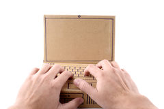 Typing on a cardboard laptop Stock Photo