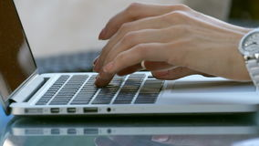 Typing female hands on keyboard. Woman work outside in cafe on laptop stock footage