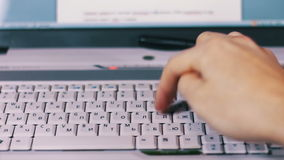 Typing Fingers Text on Computer Laptop Keyboard. A man working at a laptop sitting at a wooden table on which there are more laptop and tablet with a moving stock footage