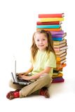 Typing girl. Portrait of cute schoolgirl looking at camera while typing on laptop keyboard with stack of books behind Royalty Free Stock Photos