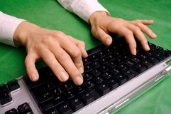 Typing on keyboard 1. Typing hands on green background royalty free stock photo