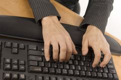 Typing on a keyboard. Detail of hands typing on a black keyboard, placed on a desk Royalty Free Stock Photo
