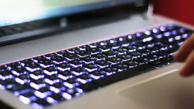 Typing on keyboard with LED Backlight. Hands typing fast on a modern laptop equipped with led backlight keyboard stock video