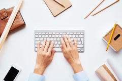 Typing on keypad. Human hands typing on keypad among business objects Royalty Free Stock Image