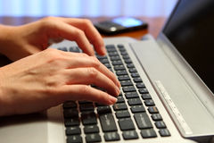 Typing on a laptop. A business person's fingers typing on a laptop with a smart phone in the background stock photography