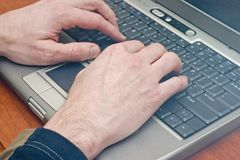 Typing on a laptop. Closeup of hands typing on a laptop Stock Image