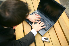Typing On Laptop. Backside caption of business man typing on laptop outdoor Royalty Free Stock Photo