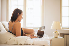 Typing on the laptop in bed Royalty Free Stock Images