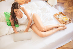 Typing on the laptop in bed Royalty Free Stock Photo