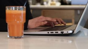 Typing on laptop with carrot juice. Writer typing on modern laptop stock footage