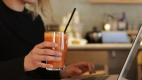 Typing on laptop with carrot juice. Writer typing on modern laptop stock video footage