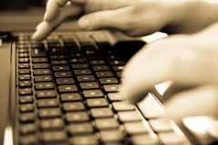Typing on laptop keyboard. Typist at work in black and white Royalty Free Stock Image