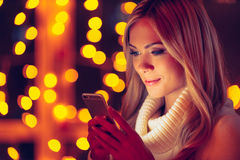 Typing lovely message to him. Beautiful young smiling woman in white sweater holding smart phone and looking at it with defocused Christmas lights in the Royalty Free Stock Image