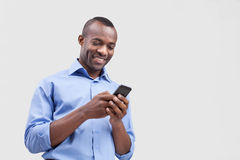 Typing a message. Cheerful black man typing something on the mobile phone and smiling while standing isolated on grey Royalty Free Stock Image