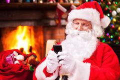 Typing message to elfs. Happy Santa Claus typing a message on the mobile phone and smiling while sitting at his chair with fireplace and Christmas Tree in the Stock Photos