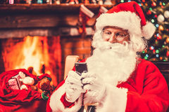 Typing message to elfs. Happy Santa Claus typing a message on the mobile phone and smiling while sitting at his chair with fireplace and Christmas Tree in the Royalty Free Stock Photo