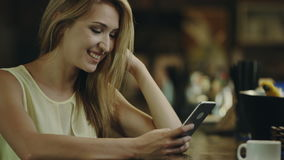 Typing on Mobile Phone in a bar. Young smiling Woman Typing on Mobile Phone in a bar, cup of coffee beside stock video footage