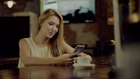 Typing on Mobile Phone in a cafe. Young smiling Woman Typing on Mobile Phone in the cafe, cup of coffee beside stock video footage