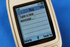 Typing a new SMS message in a cellular phone. Typing a new SMS text message in a cellular phone isolated on blue Royalty Free Stock Photo