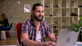 Typing nice caucasian man with great beard is smirking confidently while typing on his computer at desktop in brick. Light room, nowadays work illustration stock footage