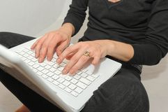 Typing on a notebook. A girl typing on a keyboard Royalty Free Stock Images