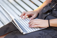 Typing on notebook... Good quality photo of a modern thin notebook (silver and white color, white keyboard, etc.) lying on womans knees. Woman in a dress is Royalty Free Stock Photography