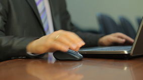 Typing on a Notebook in the office. Businessman moving a computer mouse and typing on the keyboard of a Notebook stock footage