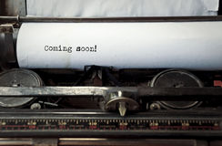 Typing on an old typewriter Coming soon. Close up image of typewriter with paper sheet and the phrase: coming soon. copy space for your text. retro filtered Stock Photography