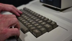 Typing on retro old fashioned personal computer closeup profile shot. Close profile shot of someone typing on an old-style 1980s personal computer. Shallow depth stock video footage